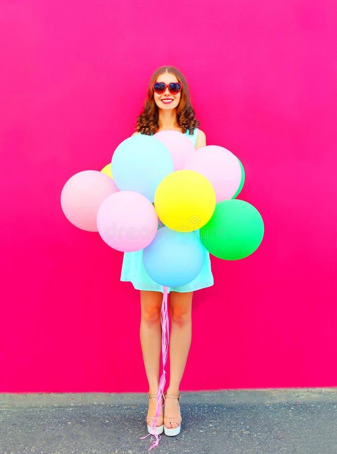有空气五颜六色的气球的愉快的微笑的少妇获得乐趣在桃红色背景的夏天 免版税库存图片