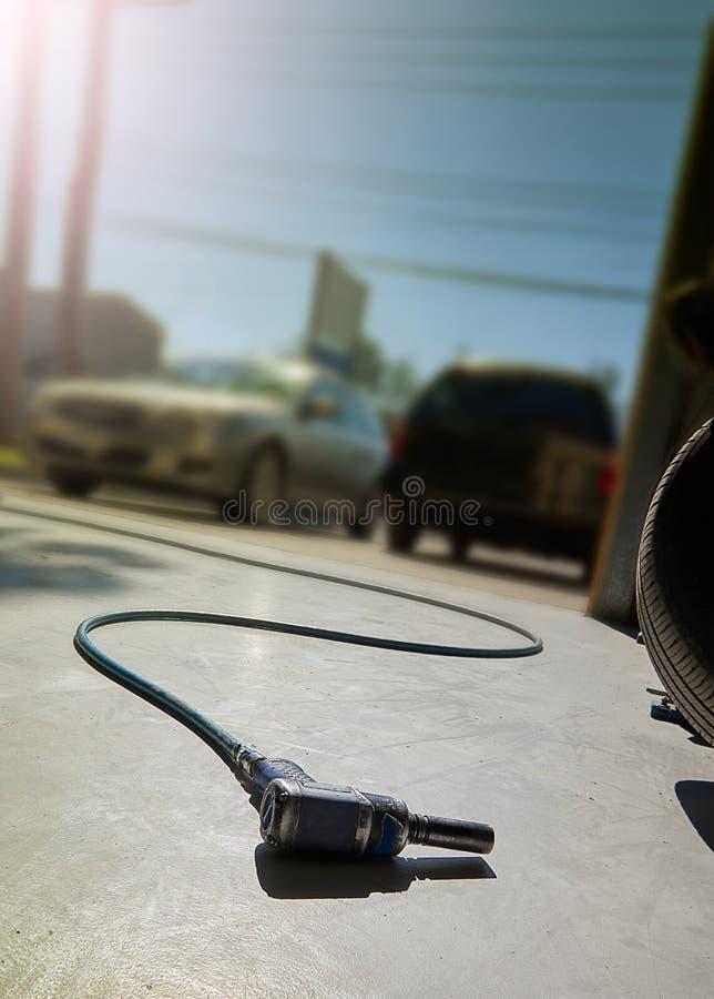 有空气软管的蓝色冲击式套筒扳手吵闹声枪在一个车间地板上有被弄脏的背景包括增加的拷贝和图表汽车 库存照片