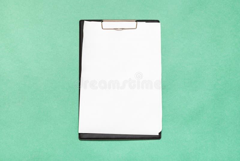 有空白白皮书板料的剪贴板在绿色 库存照片