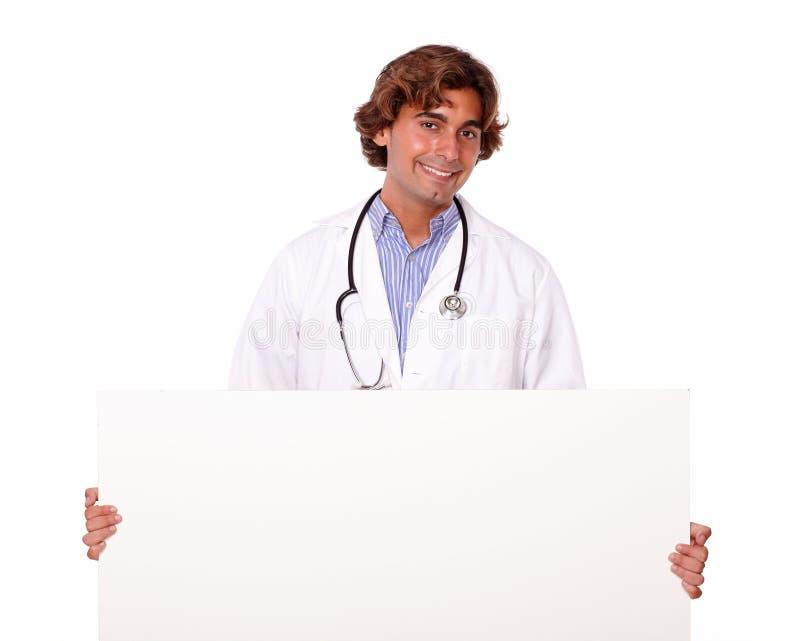 有空白的招贴的英俊的微笑的医生 库存图片