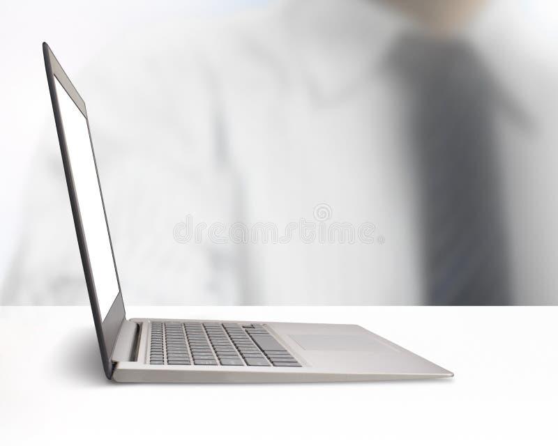 有空白的显示器屏幕的银色膝上型计算机在白色桌上 免版税库存照片