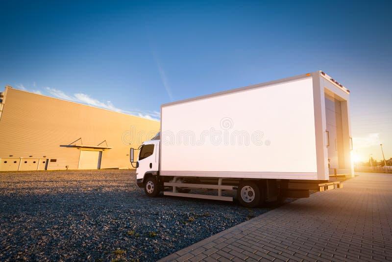 有空白的白色拖车的商业送货卡车在货物停车处 皇族释放例证