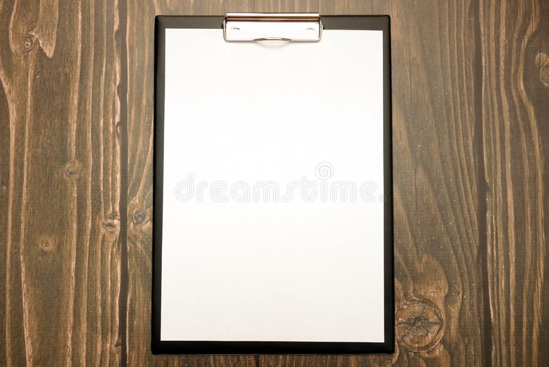 有空白的纸片的剪贴板在木背景,您的设计的拷贝空间的 库存照片