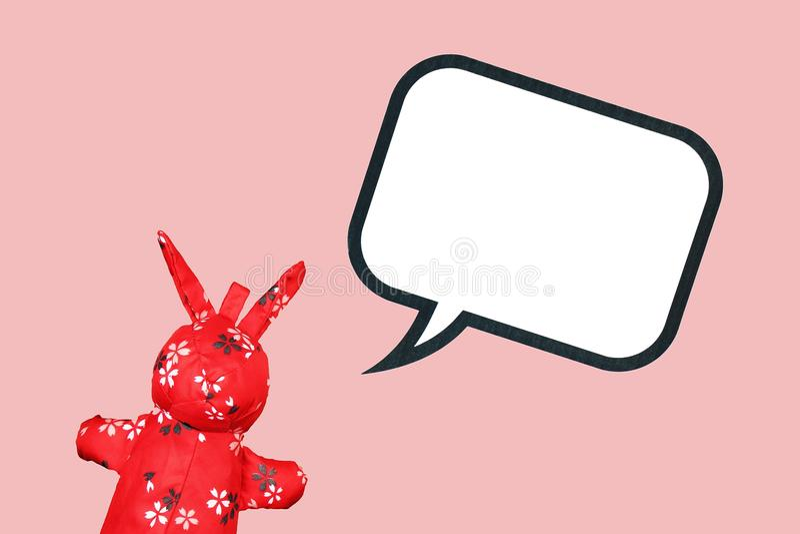 有空白的讲话泡影的红色兔子布料玩具在桃红色背景 向量例证