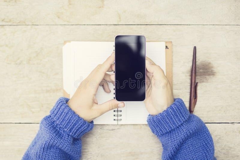 有空白的黑手机和被打开的日志的女孩在木tabl 免版税库存图片