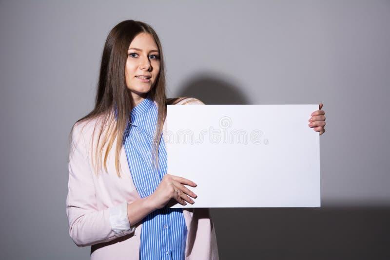有空白纸的少妇做广告的 库存照片