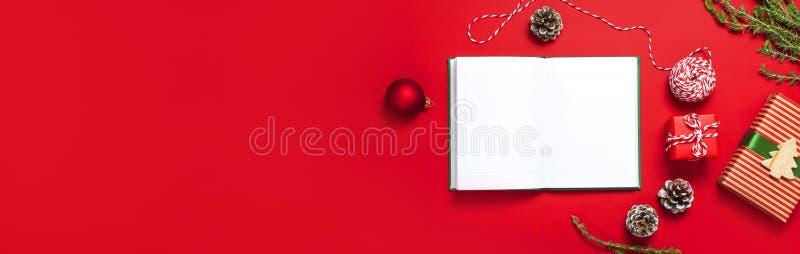 有空白页的,礼物盒,冷杉分支,在红色背景舱内甲板被放置的顶视图的球开放笔记本 圣诞节计划概念Hol 免版税库存图片