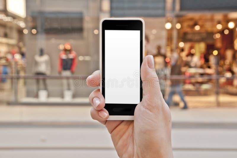 有空的屏幕的智能手机在妇女手上在购物中心 库存图片