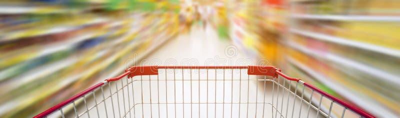 有空的红色购物车的超级市场走道 免版税库存图片
