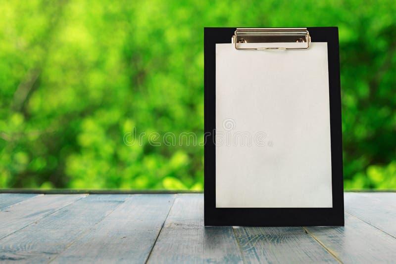 有空的纸片的剪贴板在蓝色木桌上的 免版税库存照片