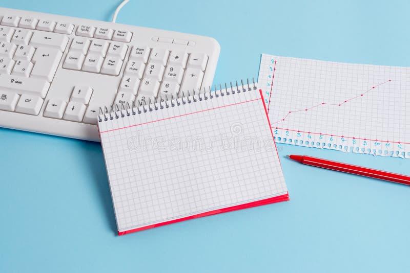有空的纸笔记、键盘和办公用具的浅兰的书桌 在提示的空格 笔记本 免版税图库摄影