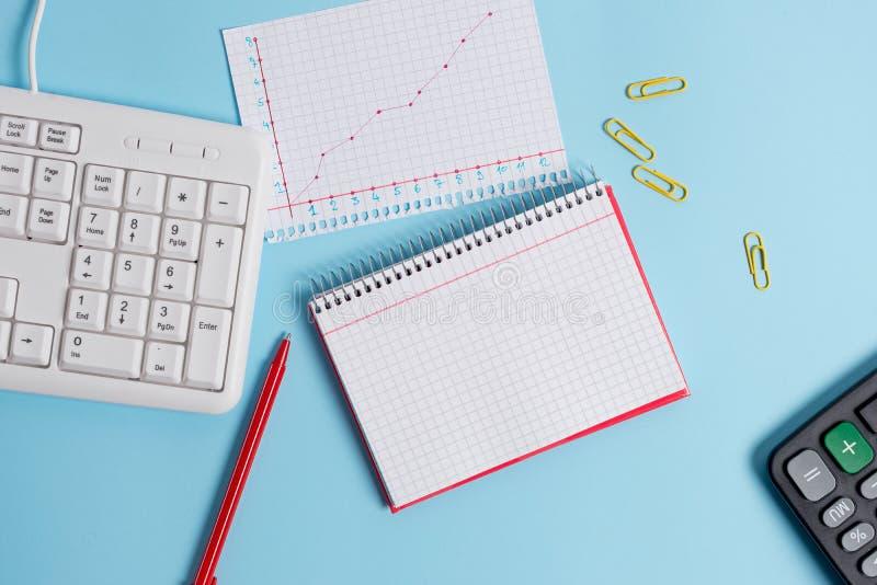 有空的纸笔记、键盘和办公用具的浅兰的书桌 在提示的空格 笔记本 库存图片