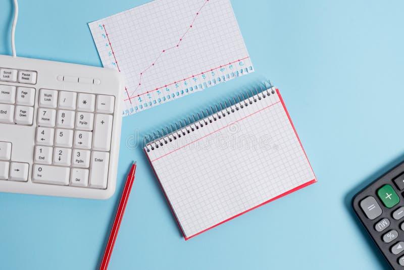 有空的纸笔记、键盘和办公用具的浅兰的书桌 在提示的空格 笔记本 免版税库存图片