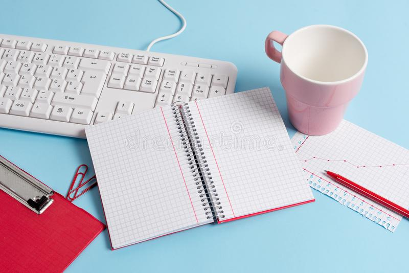 有空的纸笔记、键盘和办公用具的浅兰的书桌 在提示的空格 笔记本 库存照片