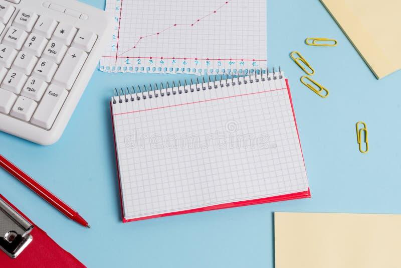 有空的纸笔记、键盘和办公用具的浅兰的书桌 在提示的空格 笔记本 免版税库存照片