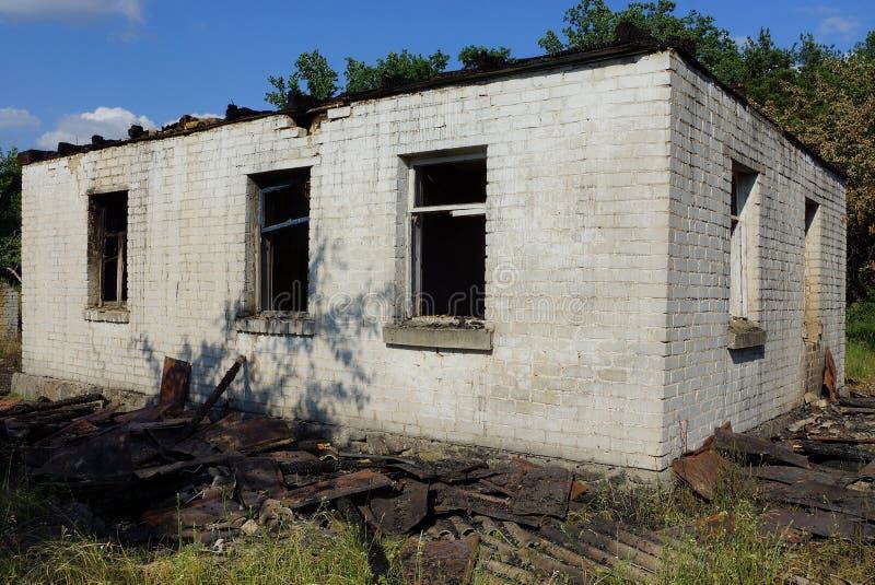 有空的黑窗口的老灰色被烧的砖房子 免版税图库摄影
