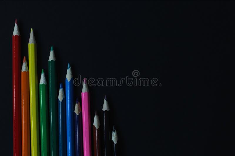 有空间的五颜六色的铅笔在黑背景的文本的 r 库存图片
