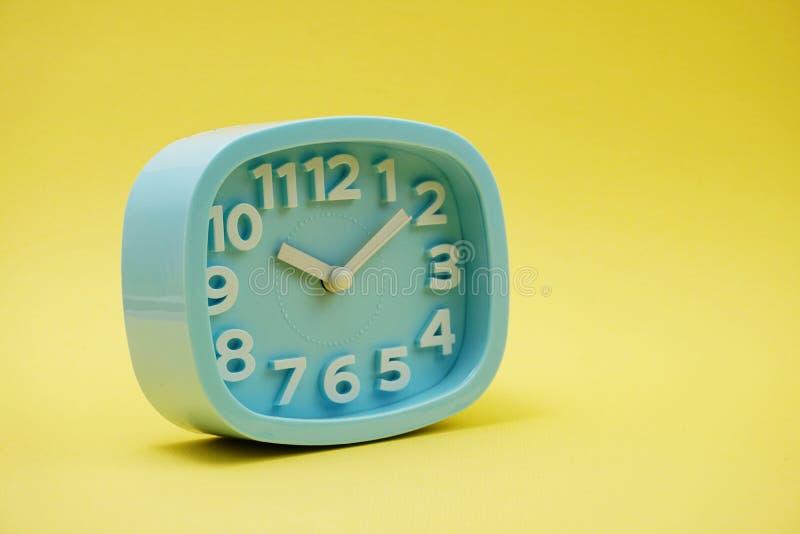 有空间的浅兰的闹钟在黄色背景 免版税库存图片