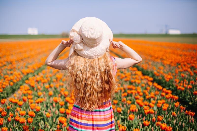 有穿一个镶边礼服和草帽的长的红色头发的美丽的年轻女人坚持在五颜六色的郁金香领域的后面 免版税库存照片