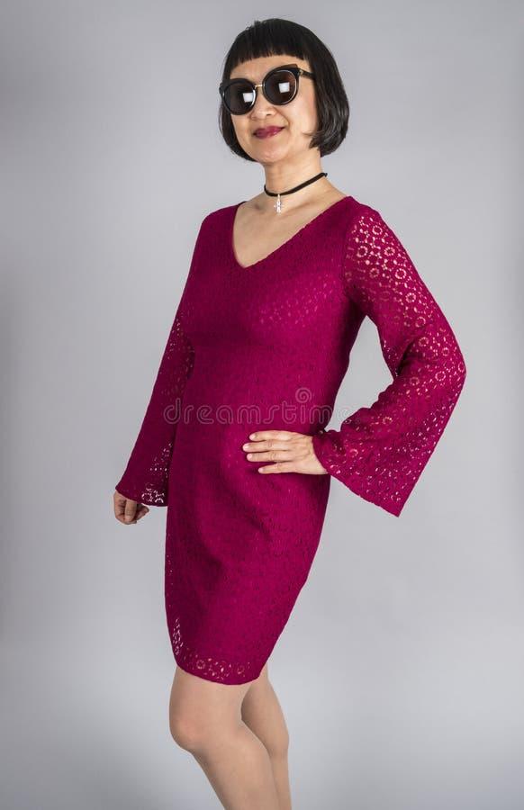 有穿一件深桃红色的有花边的礼服的短的黑发的一名亚裔妇女 免版税图库摄影