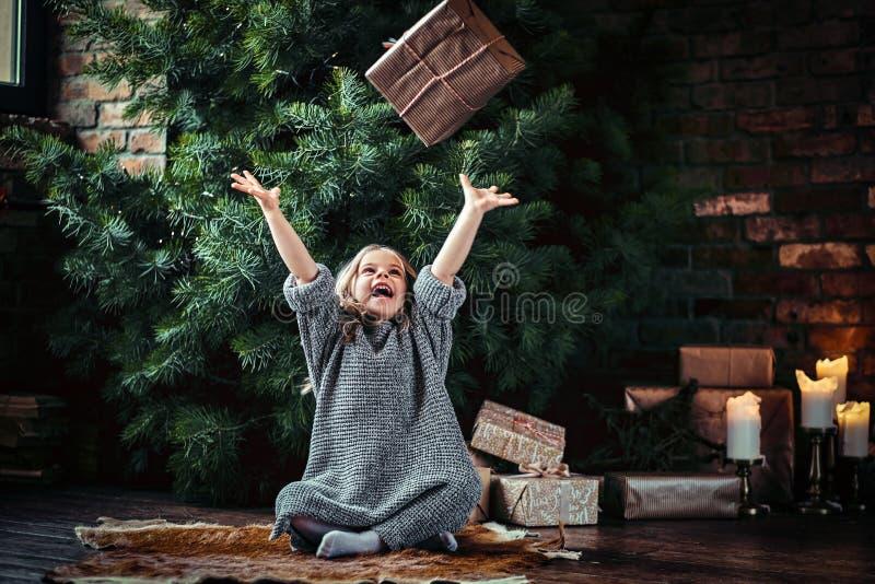 有穿一件温暖的毛线衣的白肤金发的卷发的快乐的女孩投掷礼物盒,当坐地板在旁边时 免版税库存照片
