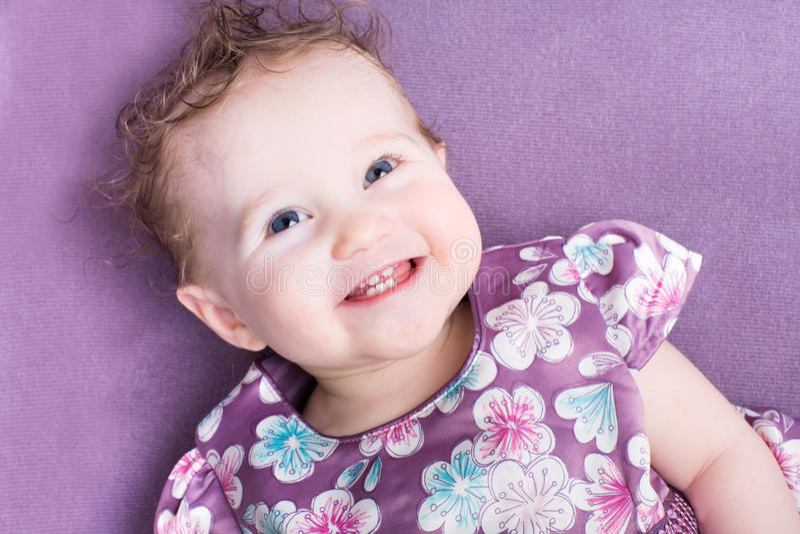 有穿一件紫色礼服的卷发的女婴 免版税库存照片