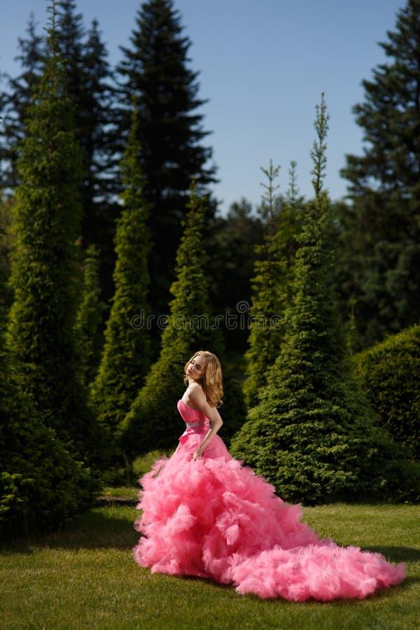 有穿与蓬松裙子的白肤金发的锁的妇女桃红色晚礼服在草的植物园里摆在 免版税库存照片
