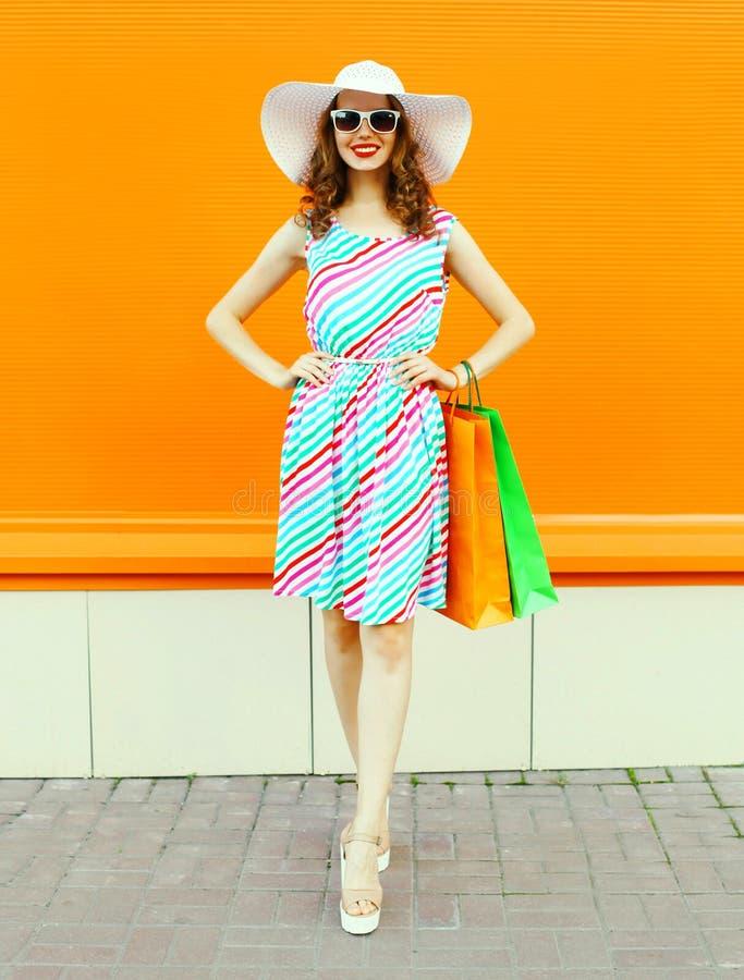 有穿五颜六色的镶边礼服,夏天草帽的购物带来的时髦的微笑的妇女摆在橙色墙壁上 免版税图库摄影
