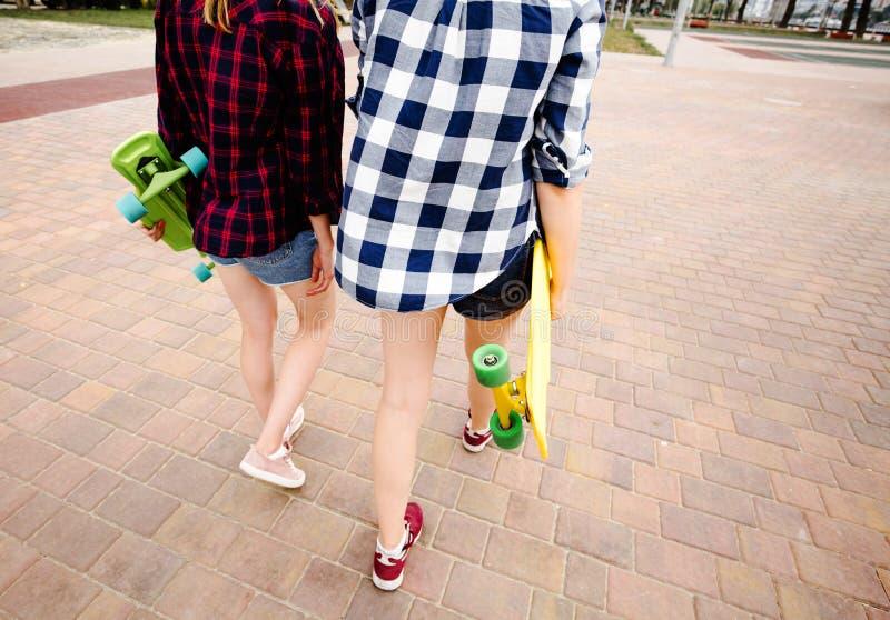 有穿方格的衬衣的longboards的两个都市女孩去沿街道在城市 库存照片