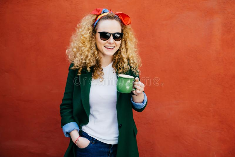 有穿时髦的夹克的头饰带的可爱的年轻欧洲拿着杯子热奶咖啡的女性和树荫有愉快的表示 免版税图库摄影