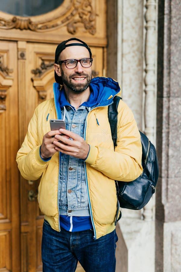 有穿时髦衣裳和拿着背包的迷人的微笑的有胡子的旅客站立户内在调查距离的画廊 免版税库存照片