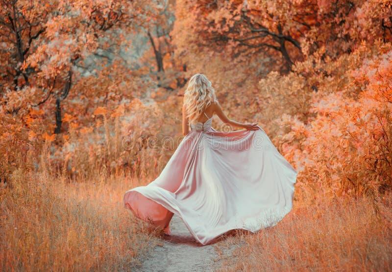 有穿有鞋带上面的长的白肤金发的卷发的年轻亭亭玉立的匀称女孩一件典雅的缎拍动丝绸桃红色礼服 图库摄影