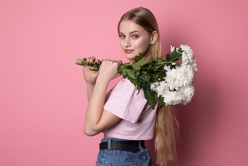 有穿桃红色T恤杉的金发的愉快的可爱的年轻女人拿着白花花束 库存照片