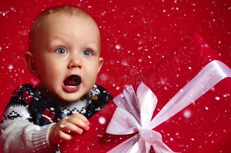有穿温暖的毛线衣的大蓝眼睛的男婴坐在他的在被包裹的箱子的礼物前面有在红色背景的丝带的 免版税图库摄影