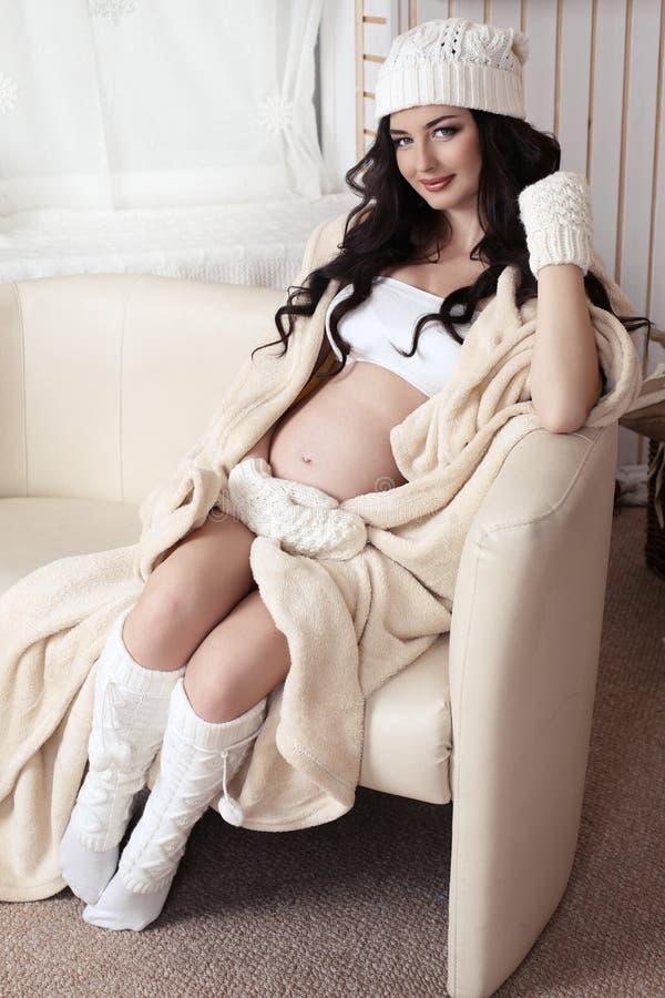 有穿温暖的被编织的衣裳的黑发的美丽的孕妇 免版税库存照片