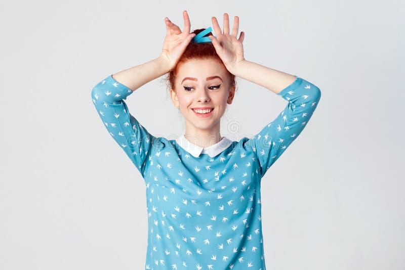 有穿蓝色礼服的美妙的微笑的惊人的红头发人女孩握在假装的头的手是兔宝宝 免版税库存图片