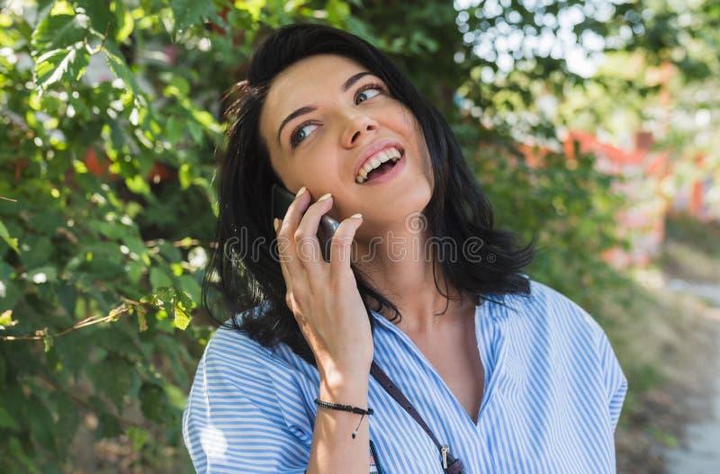 有穿蓝色衬衣的迷人的微笑的可爱的愉快的快乐的年轻白种人妇女谈话在关于planinng的手机 图库摄影