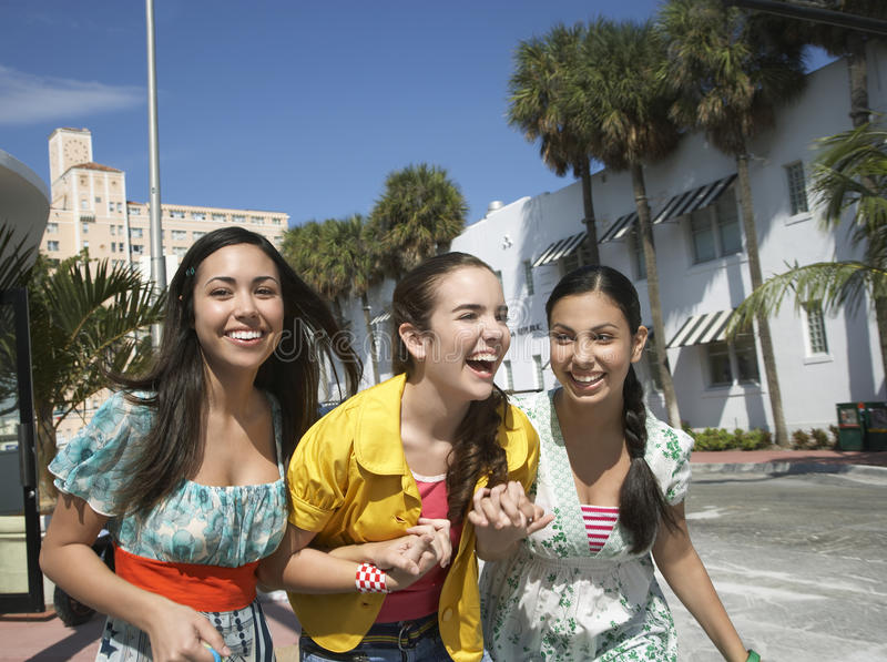 有穿过街道的购物袋的十几岁的女孩 库存图片