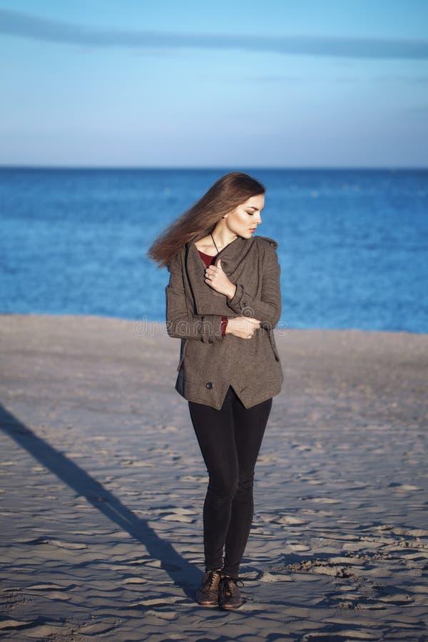 有穿黑牛仔裤的杂乱长的头发的年轻美丽的妇女和短的外套在室外有风秋天秋天的天在岸靠岸 免版税库存照片