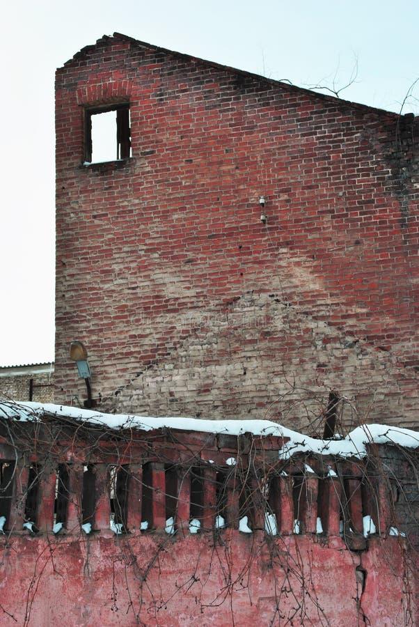 有窗口孔的被破坏的红砖墙壁,积雪的篱芭墙壁 库存照片