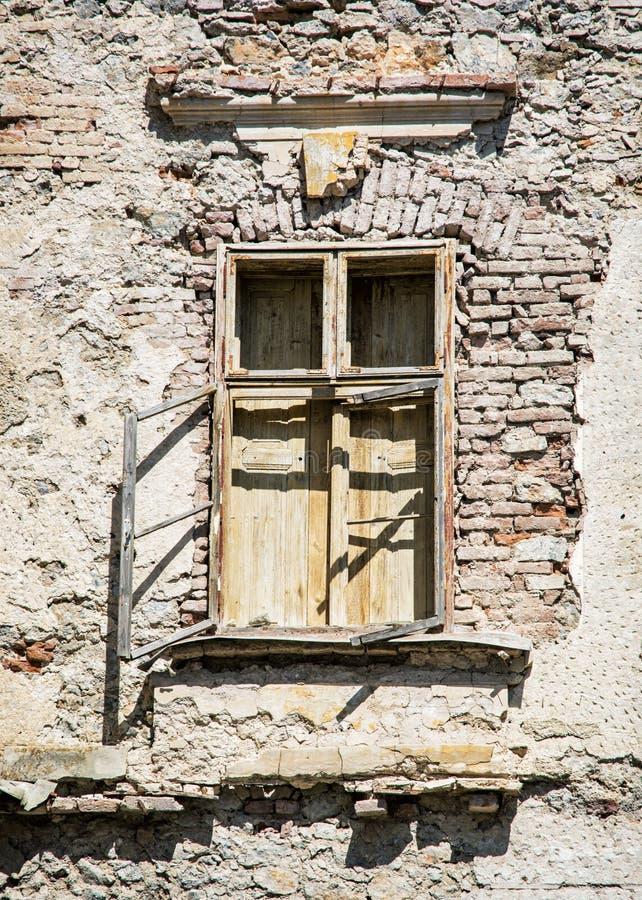 有窗口的老损坏的砖墙 库存照片