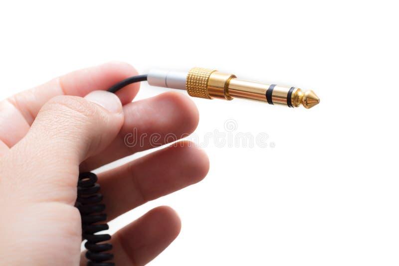 有立体声音频在whi隔绝的缆绳馏金的适配器的手 库存图片