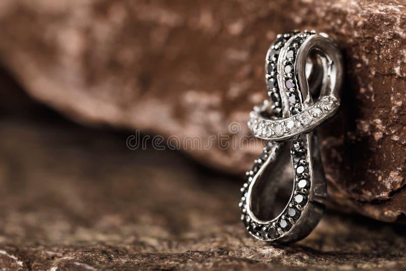 有立方体氧化锆的人造白金耳环在与拷贝空间的石头 库存照片