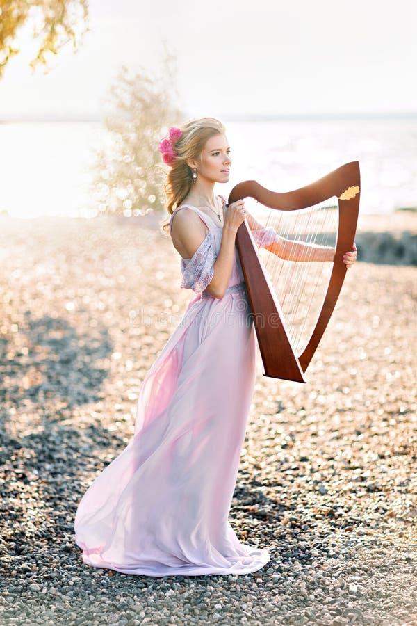 有竖琴的美丽的妇女 库存照片