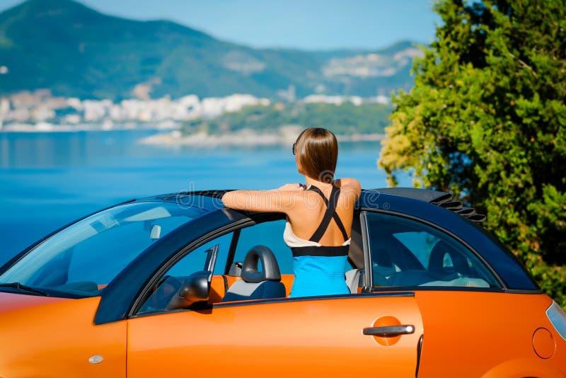 有站立与橙色敞蓬车的长发的美丽的年轻女人在陆间海海岸 免版税库存照片