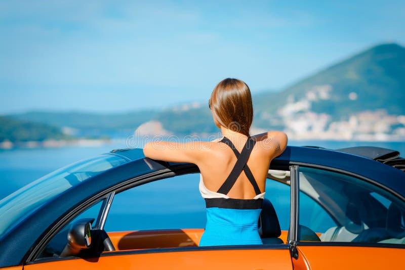 有站立与橙色敞蓬车的长发的美丽的年轻女人在陆间海海岸 库存照片