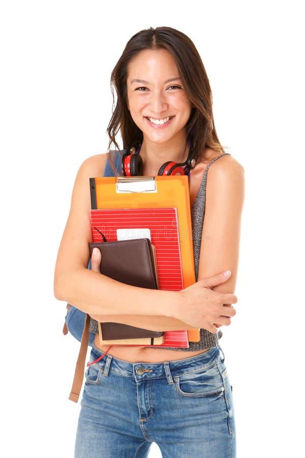 有站立反对被隔绝的白色背景的书的微笑的亚裔女生 免版税库存照片