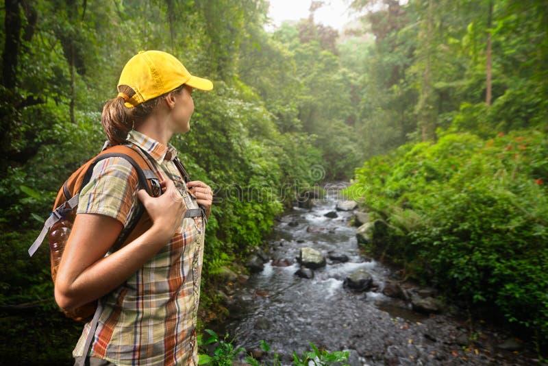 有站立和享用雨林的背包的妇女远足者和 库存照片