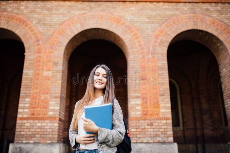 有站立和微笑在公园的背包和笔记本的快乐的可爱的少妇 图库摄影