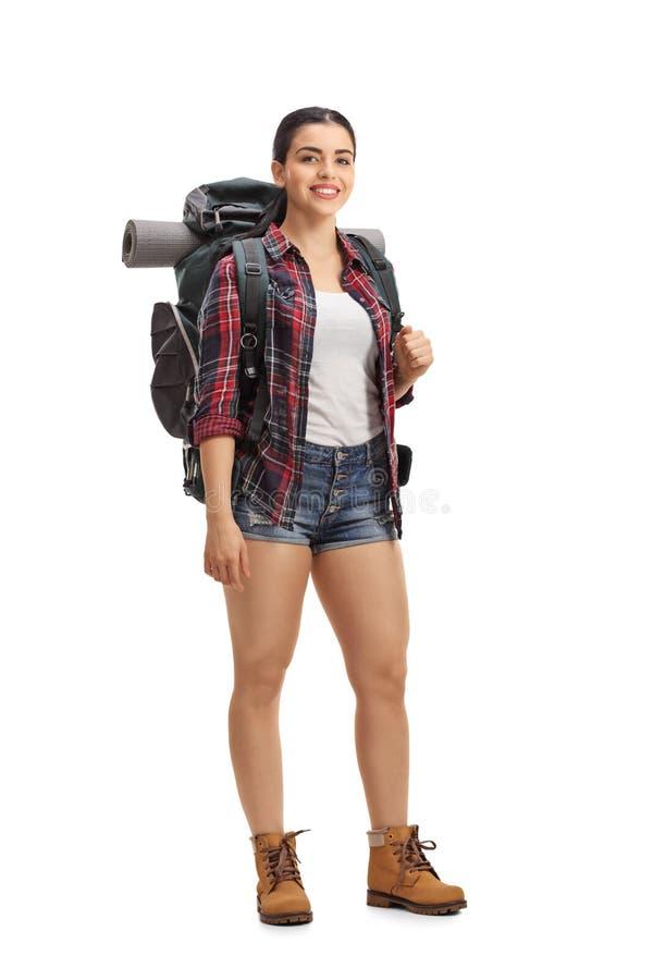 有站立和看照相机的背包的女性徒步旅行者 库存照片